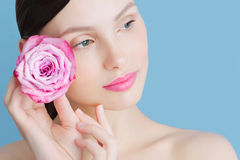 Portrait of a beautiful brunette girl with a pink rose on a blue background Stock Photo