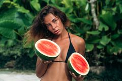 Portrait beautiful brunette girl in swimsuit with watermelon fruit holding in hands. Sexy model with perfect body, cute. Smile posing. Concept of sport Royalty Free Stock Photography