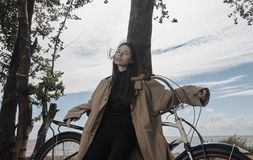 Portrait of beautiful brunette girl wearing raincoat with bicycle royalty free stock photos