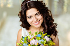 Portrait of a beautiful brunette girl in white dress with charming toothy smile and a bouquet of wildflowers on a background of b royalty free stock image