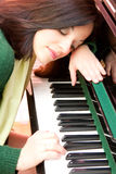 Portrait of a beautiful brunette and her piano. Portrait of a beautiful brunette playing at her piano Stock Image