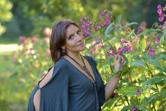 Portrait of a beautiful brunette next to pink flowers in the garden Stock Photo
