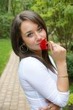 Portrait of beautiful brunette outdoors holding a red flower Stock Photography