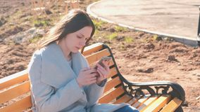 Portrait of beautiful brunette reading and typing a message in her phone sitting on the bench in park. Portrait of beautiful brunette reading and typing a stock video footage