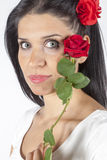 Portrait of beautiful brunette with red rose. Portrait of yong beautiful woman looking at camera with red rose in hair Royalty Free Stock Image