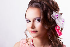 Portrait of a beautiful brunette in the spring image with flower. Portrait of curly brunette with purple make-up in pink dress with soutache technique Stock Photos