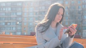 Portrait of beautiful brunette typing a message in her phone in the courtyard of a multi-storey building. Portrait of beautiful brunette typing a message in her stock footage