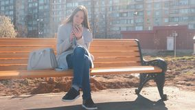 Portrait of beautiful brunette typing a message in her phone in the courtyard of a multi-storey building. Portrait of beautiful brunette typing a message in her stock video footage