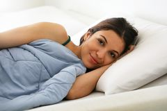 Portrait of beautiful brunette waking up looking at camera at home in bed. royalty free stock photos