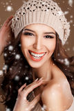 Portrait of a beautiful brunette in the winter. Closeup of a young, brown-eyed woman, with long, curly dark hair,knitted light brown hat, with bare shoulders royalty free stock photography
