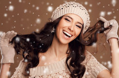 Portrait of a beautiful brunette in the winter. Closeup of a young, brown-eyed woman, with long, curly dark hair,knitted light brown hat, with bare shoulders royalty free stock images