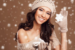 Portrait of a beautiful brunette in the winter. Closeup of a young, brown-eyed woman, with long, curly dark hair,knitted light brown hat, with bare shoulders stock images