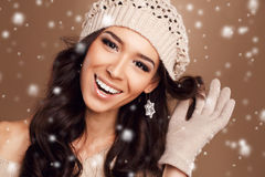 Portrait of a beautiful brunette in the winter. Closeup of a young, brown-eyed woman, with long, curly dark hair,knitted light brown hat, with bare shoulders stock image