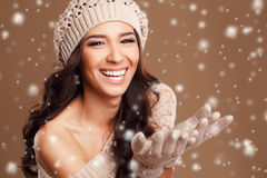 Portrait of a beautiful brunette in the winter. Closeup of a young, brown-eyed woman, with long, curly dark hair,knitted light brown hat, with bare shoulders royalty free stock image