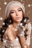 Portrait of a beautiful brunette in the winter. Closeup of a young, brown-eyed woman, with long, curly dark hair,knitted light brown hat, with bare shoulders stock photos