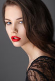 Portrait of beautiful brunette woman in black dress and red lips Stock Photography