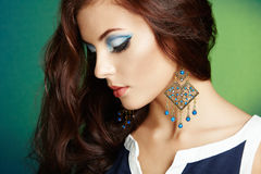 Portrait of beautiful brunette woman with earring. Perfect makeu Royalty Free Stock Photo