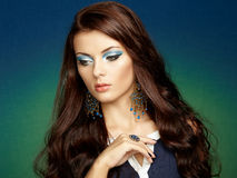 Portrait of beautiful brunette woman with earring. Perfect makeu Royalty Free Stock Photography