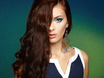 Portrait of beautiful brunette woman with earring. Perfect makeu Stock Photography