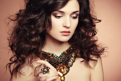 Portrait of beautiful brunette woman with earring. Perfect makeu Stock Images