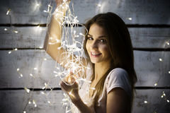 Portrait of beautiful brunette woman holding glowing christmas garland in hands Royalty Free Stock Image