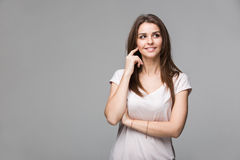 Portrait of beautiful brunette woman with natural make-up, on grey background Royalty Free Stock Photo