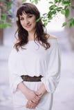 Portrait of a beautiful brunette woman outdoors in a white dress. Close-up portrait. Summer outdoor portrait Stock Photos