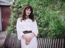 Portrait of a beautiful brunette woman outdoors in a white dress. royalty free stock photos
