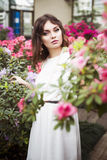 Portrait of a beautiful brunette woman in pink dress and colorful make up outdoors in azalea garden Stock Photos