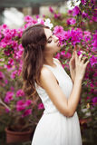 Portrait of a beautiful brunette woman in pink dress and colorful make up outdoors in azalea garden Royalty Free Stock Photos