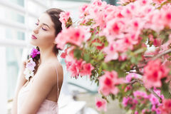 Portrait of a beautiful brunette woman in pink dress and colorful make up outdoors in azalea garden.  stock photography