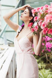 Portrait of a beautiful brunette woman in pink dress and colorful make up outdoors in azalea garden Royalty Free Stock Images