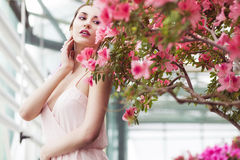 Portrait of a beautiful brunette woman in pink dress and colorful make up outdoors in azalea garden Royalty Free Stock Photography