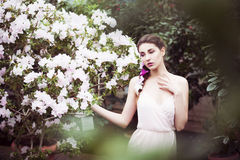 Portrait of a beautiful brunette woman in pink dress and colorful make up outdoors in azalea garden Stock Photo