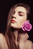 Portrait of beautiful brunette woman with rose Stock Image