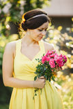 Portrait of beautiful brunette woman with stylish haircut in yellow dress holding red roses and posing. Romantic retro look of pre Royalty Free Stock Photography