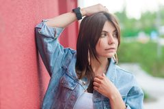 Portrait of beautiful brunette young woman with makeup in denim casual style standing, posing with hand on head and looking away royalty free stock image