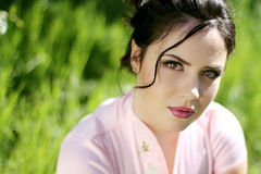 Portrait of Beautiful Brunette Young Woman resting over green gr Royalty Free Stock Photography