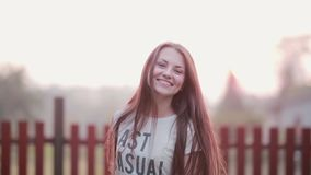 Portrait of beautiful brunette young woman smiling outdoor, turns and looking at camera cheerful on sunset stock footage