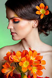 Portrait of a beautiful brunnette with orange flowers Royalty Free Stock Photography