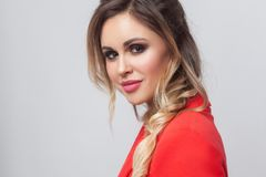 Portrait of beautiful business lady with hairstyle and makeup in red fancy blazer standing and looking at camera with smile stock images