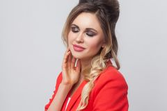 Portrait of beautiful business lady with hairstyle and makeup in red fancy blazer standing and touching her face and smiling with royalty free stock photos