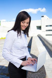 Portrait of beautiful business woman with laptop on the street Stock Photo