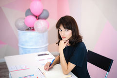Portrait of a beautiful business woman making notes in a notebook. Holds a pen, sitting in the workplace in a pink office Stock Photography