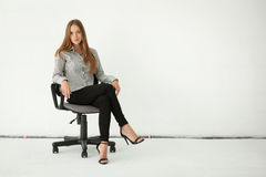 Portrait of beautiful business woman sitting on chair against wh Royalty Free Stock Photos