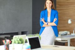 Portrait of a beautiful business woman standing near her workplace. Royalty Free Stock Photo