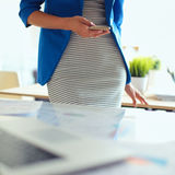 Portrait of a beautiful business woman standing near her workplace. Royalty Free Stock Images