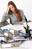 Portrait of beautiful business woman surrounded by big pile of d Royalty Free Stock Photography