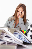 Portrait of beautiful business woman surrounded by big pile of d Stock Images