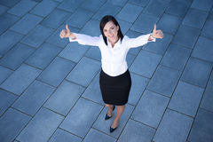 Portrait of beautiful business woman thumbs up over tiled floor Royalty Free Stock Photos